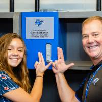"Two guests using the ""Laker for a Lifetime"" gesture to point at a named locker at the Jamie Hosford Football Center dedication."